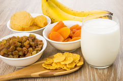 Dried fruits, spoon with corn flakes, bananas and glass milk Stock Photos
