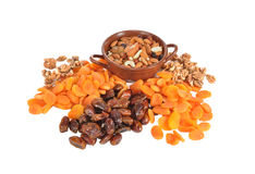 Dried fruits on a table. The dried apricots, nuts, dates, ceramic vase lay on a table Royalty Free Stock Photo