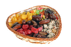 Dried fruits in a wattled basket. Multi-coloured dried fruits in a wattled basket separately on a white background Stock Images