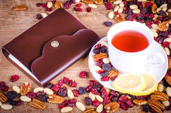 Dried fruits  with white cup of tea, saucer and notebook Stock Photos