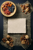 Dried fruits in a wicker vase and nuts. Dried fruits in a wicker vase and nuts on sackcloth. A sheet of paper for an inscription. Directly above royalty free stock photos