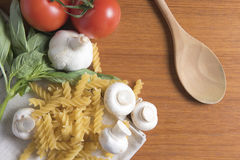 Dried fusilli pasta with tomatoes, basil and garlic Stock Image