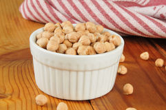 Dried garbanzo beans. A cup of dried garbanzo beans on a rustic wooden cutting board royalty free stock photos