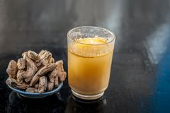 Dried ginger with its extraced water or juice. Dried ginger or Zingiber officinale or Soth,Sonth with ayurvedic medicinal extracted juice in a transparent glass Royalty Free Stock Photo
