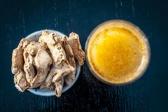 Dried ginger with its extraced water or juice. Dried ginger or Zingiber officinale or Soth,Sonth with ayurvedic medicinal extracted juice in a transparent glass Stock Images
