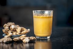 Dried ginger with its extraced water or juice. Dried ginger or Zingiber officinale or Soth,Sonth with ayurvedic medicinal extracted juice in a transparent glass Stock Image