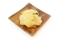 Dried ginger wiht sugar on a wooden plate Royalty Free Stock Photography