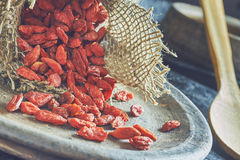 Dried goji berries. Coming out of small burlap bag Stock Photos