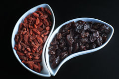 Dried goji berries and dark grapes in white bowls on a black background.  Royalty Free Stock Photography