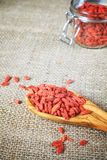 Dried goji berries on a wooden spoon and linen background. Stock Photography