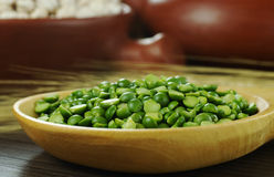 Dried Green Peas. On wooden spoon with crop and bowls in the background (Selective Focus, Focus on the green peas Stock Image