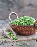 Dried green split peas in a copper plate on a wooden table Royalty Free Stock Photos