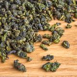 Dried green tea closeup on a wooden background Royalty Free Stock Photos