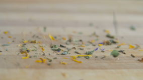 Dried green tea leaves falling on a wooden surface stock footage