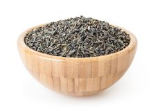 Dried green tea leaves in wooden bowl isolated on white background. With clipping path royalty free stock image