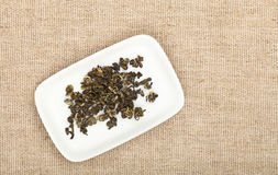 Dried green tealeaves plate on canvas tablecloth. White small plate with dried green tea leaves on flax canvas tablecloth, close up, elevated top view, directly Royalty Free Stock Photo