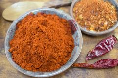 Dried grounded, chopped and whole peppers in natural wooden bowl Stock Photography
