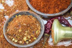 Dried grounded, chopped and whole peppers in natural wooden bowl Royalty Free Stock Photos