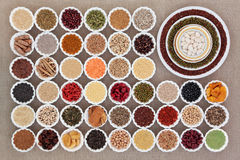 Dried Health Food Sampler. Large dried health food sampler in china bowls forming an abstract background over hessian. High in antioxidants, vitamins, minerals Stock Photo