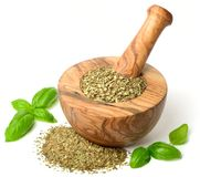 Dried herb, basil leaves in the wooden mortar, isolated on white. Background stock photo