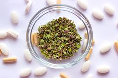 Dried herbs in a bowl on nutritional supplements pills background. Alternative herbal medicine, naturopathy and homeopathy stock images