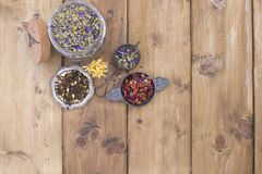 Dried herbs and flowers for tea. Wooden background and free space for text or cards. royalty free stock photos