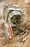 Dried herbs in glass bottle. Dried cooking herbs in an opened glass bottle lying on its side spilling out onto an old rustic wooden tabletop royalty free stock photo