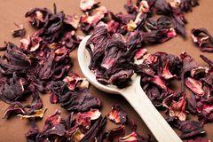 Dried hibiscus flower in a spoon on a brown table royalty free stock image