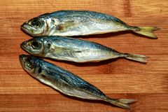 Dried horse mackerel is silver in color three pieces are on the Board from bamboo. Dried horse mackerel is silver in color three pieces are on the orange Board Royalty Free Stock Photo