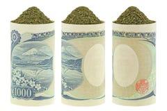 Dried Japanese green tea inside rolls of Japanese Yen banknotes Stock Photos