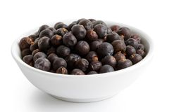 Dried juniper berries in white ceramic bowl. stock photo