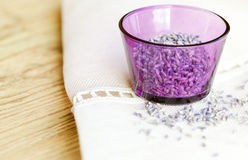 Dried lavender flowers in purple glass on fabric Royalty Free Stock Photography