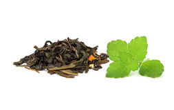 Dried leaves of green tea with a sprig of mint. Stock Photo