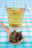 Dried lemon balm with spoon and glass of herbal drink on tablecloth Stock Images