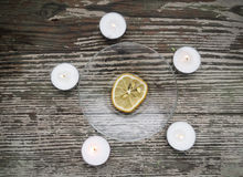 The dried lemon is surrounded of candles Stock Images