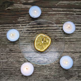 The dried lemon is surrounded of candles Royalty Free Stock Images