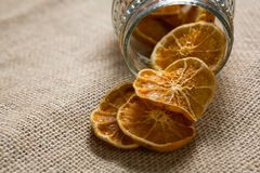 Dried lemons spilling out of jar Stock Images