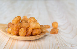 Dried longan with wooden spoon and table Royalty Free Stock Photo