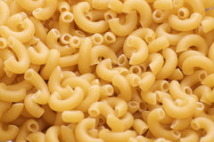 Dried Macaroni. Uncooked macaroni noodles used as a carbohydrate background Royalty Free Stock Images