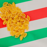 Dried Macaroni on the background of the Italian flag colors, place for writing text around it Stock Images