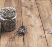 Dried mallow flowers in a jar on a wooden background. Free space for text. Copy space.  Royalty Free Stock Images