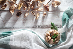 Dried and marinated mushrooms in crate on wooden background Royalty Free Stock Images