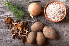 Dried mashrooms, potato, onion, dill and grain in a bowl on a ol. D wooden board Royalty Free Stock Photos