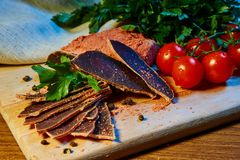 Dried meat, basturma lies on a wooden Board with capers and spices. fresh parsley and red cherry tomatoes stock photo