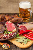 Dried meat still life. Beer set with red pepper on the cutting board Royalty Free Stock Photos