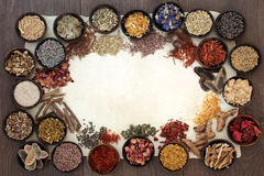 Dried Medicinal Herbs and Flowers. Dried medicinal herb and flower selection used in natural alternative medicine on parchment paper forming a border on oak Royalty Free Stock Images