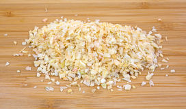 Dried minced onions on wood cutting board Royalty Free Stock Photos