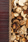 Dried mushroom lying on dark bamboo mat, for menu Stock Photo