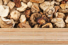 Dried mushrooms and bamboo mat Royalty Free Stock Images