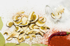 Dried mushrooms Boletus reticulatus with bay leaves, chili, red peppers. Stock Photo
